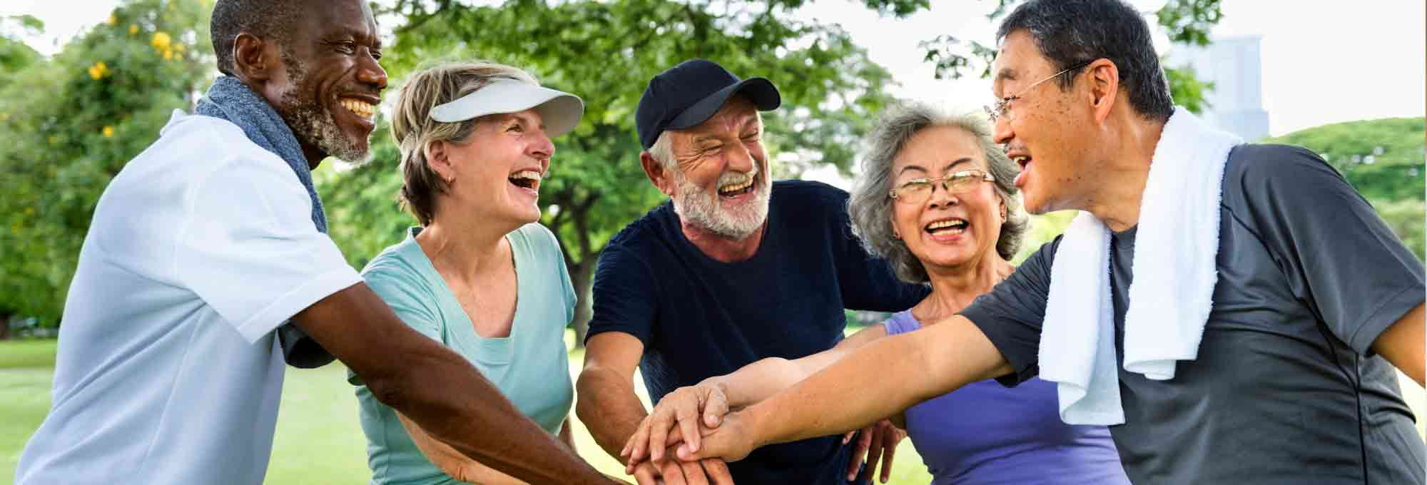 Photograph of five senior citizens enjoying time together in a park.
